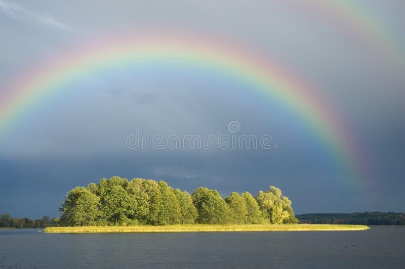 Arco iris sobre una isla imagen de archivo