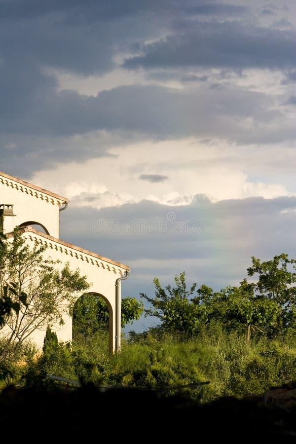 Arco iris y cielo tempestuoso sobre casa fotografía de archivo