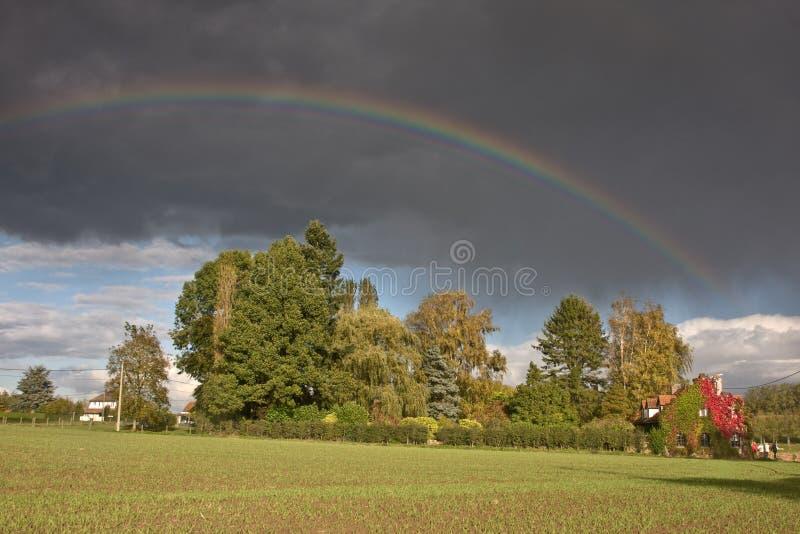 Arco iris y lluvia sobre un campo fotos de archivo libres de regalías