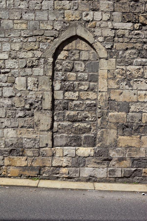 Arco medievale in un fondo della parete di pietra fotografia stock libera da diritti
