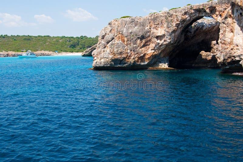 Arco natural e barco recreacional em Cala Antena fotografia de stock royalty free