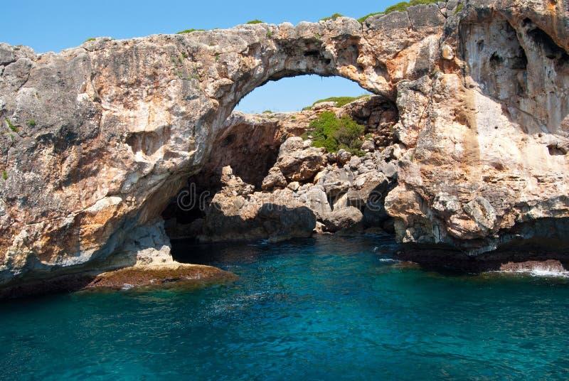 Arco natural e o grotto em Cala Antena imagem de stock