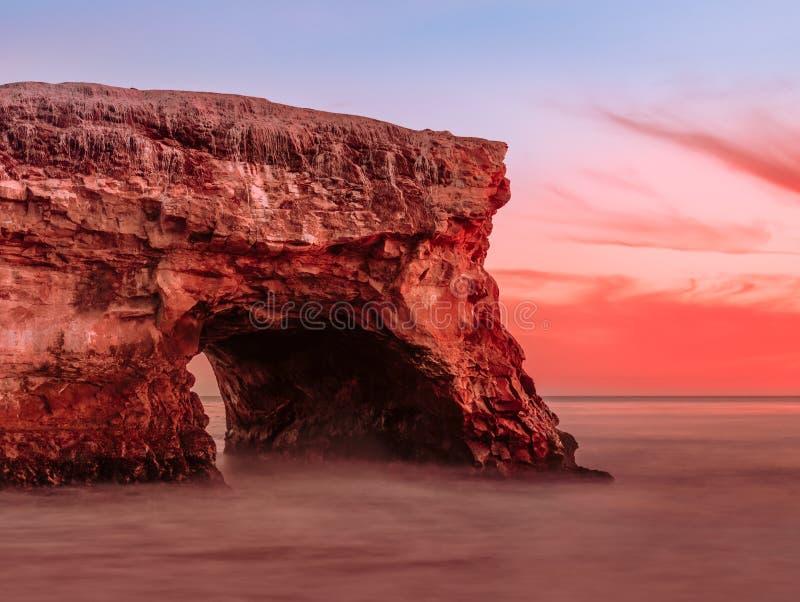 Arco natural increíble en la roca enorme en la puesta del sol imagen de archivo