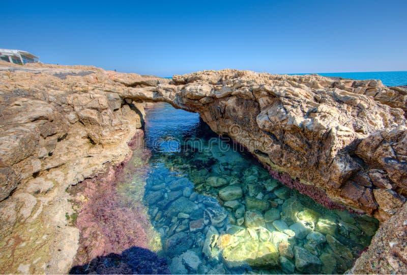 Arco naturale naturale sopra uno stagno di marea alla spiaggia fotografia stock libera da diritti