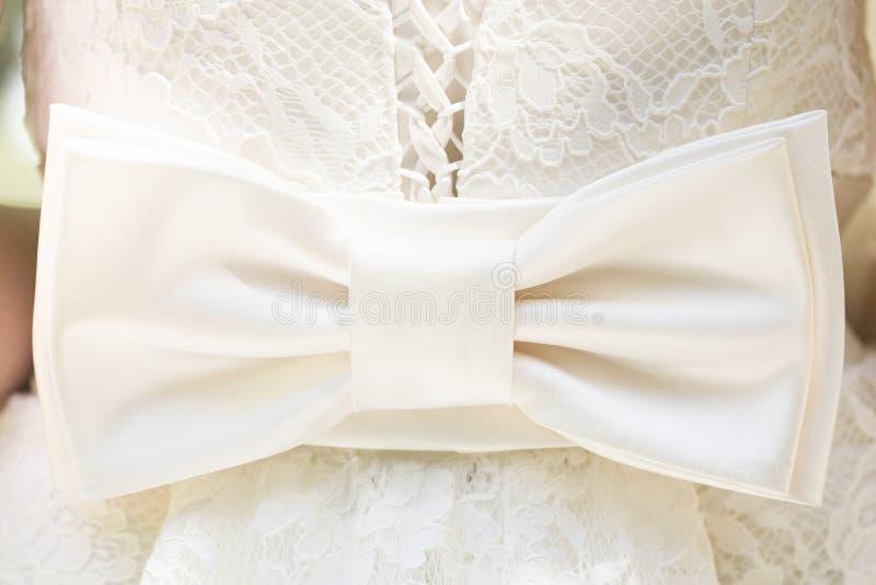 Arco o nastro bianco sul vestito da sposa dal pizzo fotografie stock