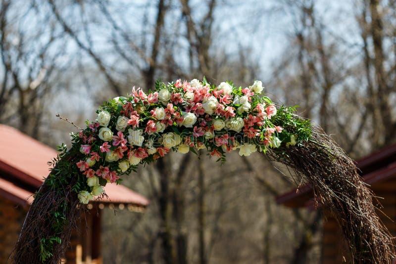 Arco que se casa redondo de las ramas adornadas con las flores y la decoración alrededor de ella fotografía de archivo libre de regalías
