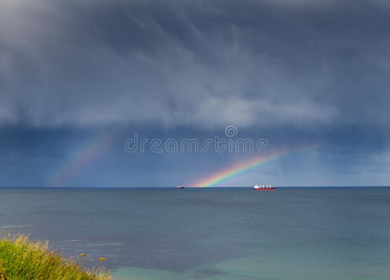 Arco-?ris dobro para fora no mar sobre alguns barcos foto de stock