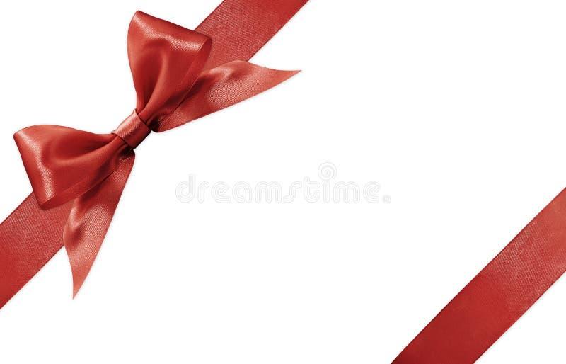 Arco rojo de la cinta de satén aislado en el fondo blanco foto de archivo