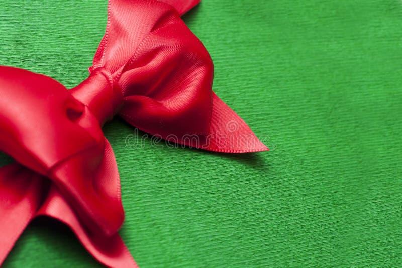 Arco rojo de la cinta en backround verde del papel de embalaje con el espacio de la copia foto de archivo