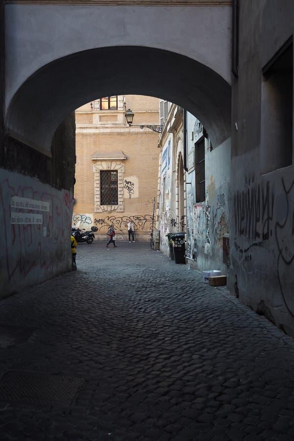 Arco a Roma, Italia con due persone che passano vicino immagine stock libera da diritti