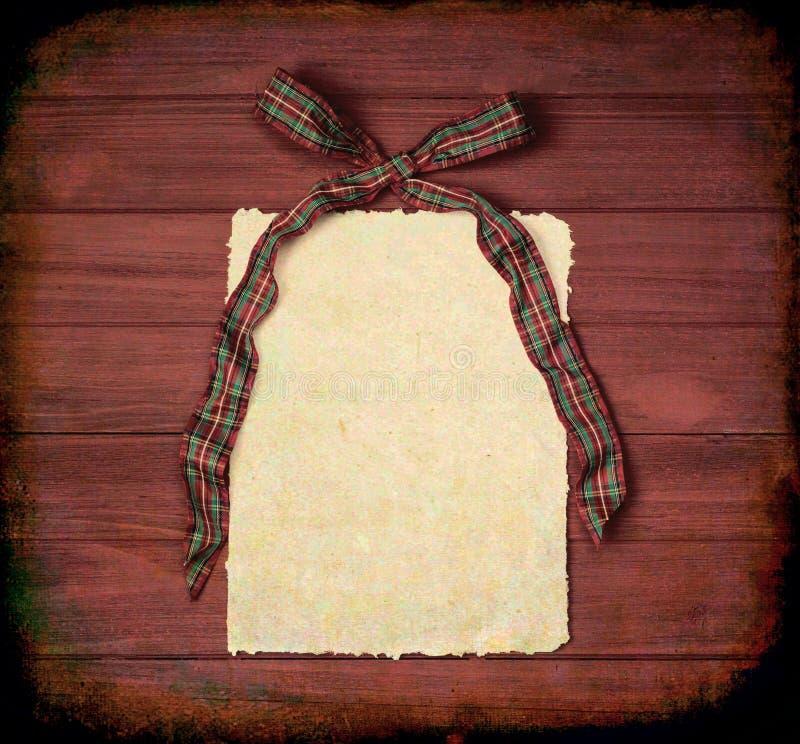 Arco rosso e verde di Natale del plaid con carta con i bordi irregolari sul fondo di legno rustico dei bordi di Brown con lo spaz immagini stock