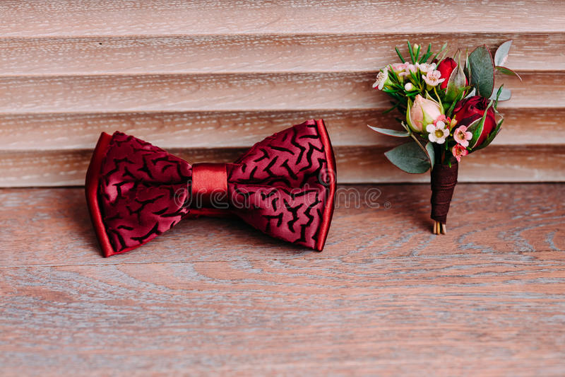 Arco y boutonniere rojos elegantes en el fondo de madera, novio que consigue listo por mañana antes de la boda fotos de archivo