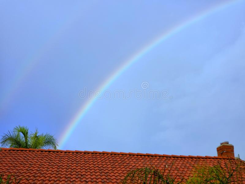 Arcobaleno della curva attraverso un tetto immagini stock libere da diritti