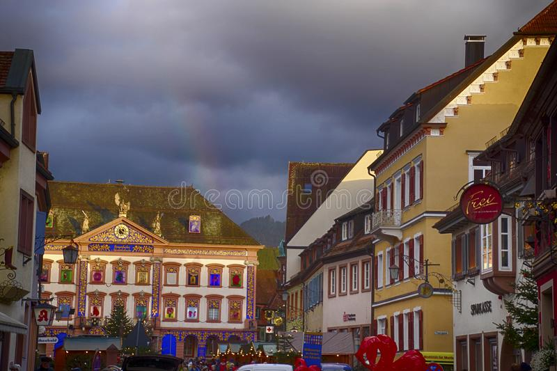 Arcobaleno dietro la casa decorata di arrivo al mercato di Natale fotografie stock