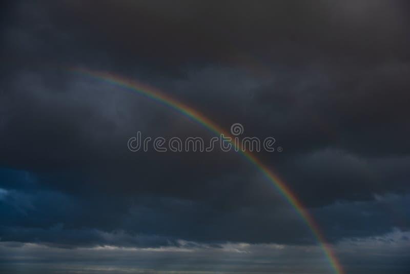 Arcobaleno fra le nuvole scure per simbolizzare energia positiva fotografia stock libera da diritti