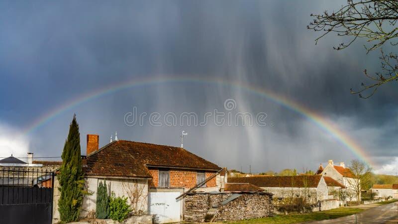 Arcobaleno pieno sopra la piccola città La Borgogna, Francia fotografie stock