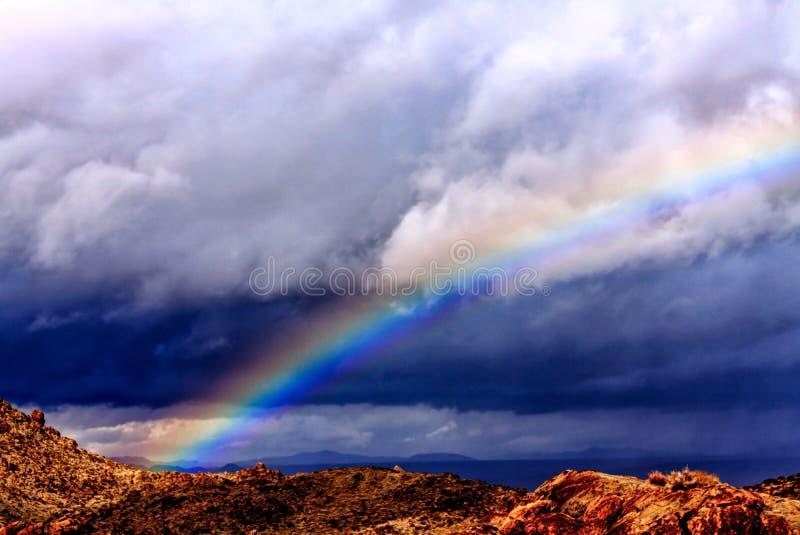 Arcobaleno profondo sotto le nuvole scure immagini stock libere da diritti