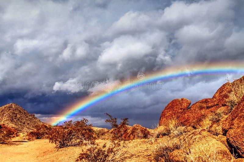 Arcobaleno profondo sotto le nuvole scure immagine stock