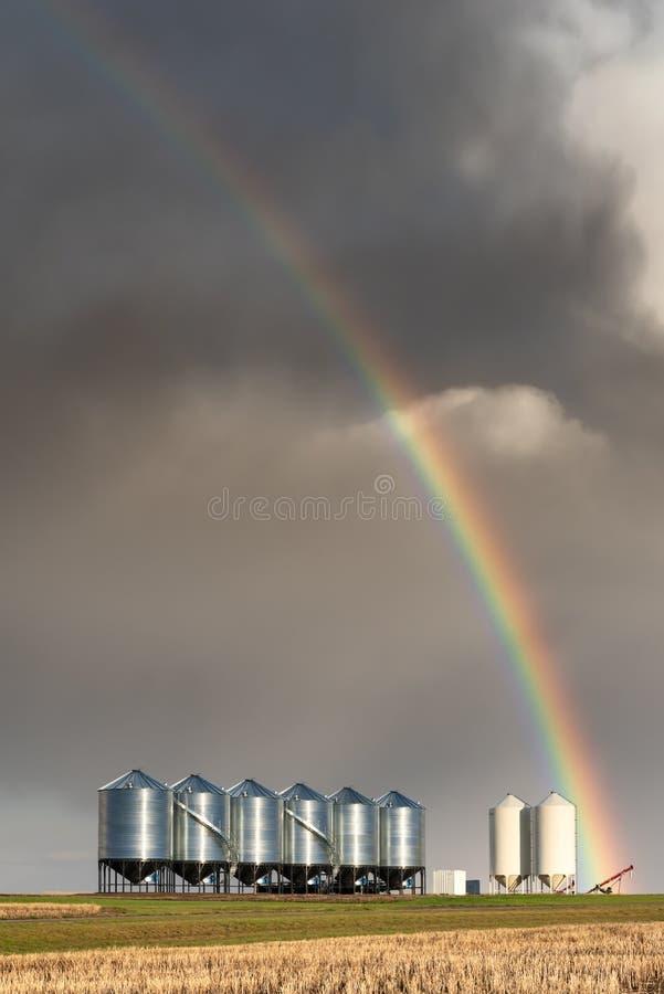 Arcobaleno sopra i recipienti del grano durante la tempesta della molla in Saskatchewan fotografie stock libere da diritti