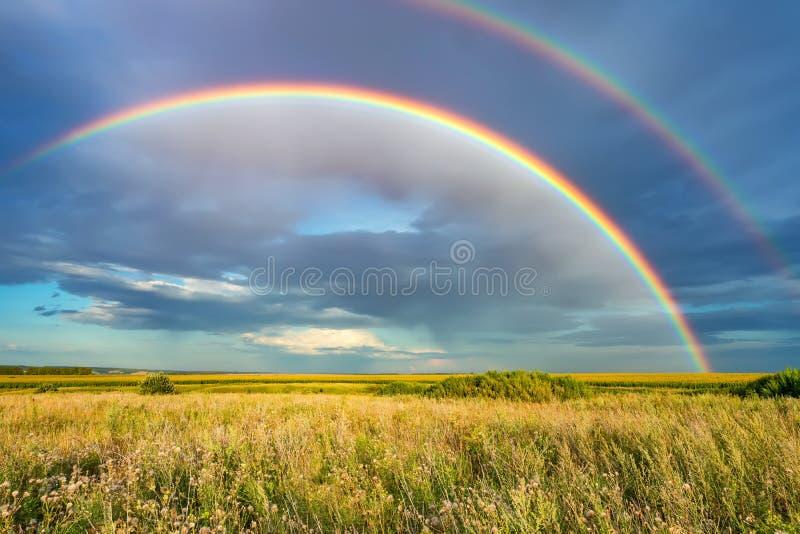 Arcobaleno sopra il cielo tempestoso in campagna al giorno di estate immagini stock