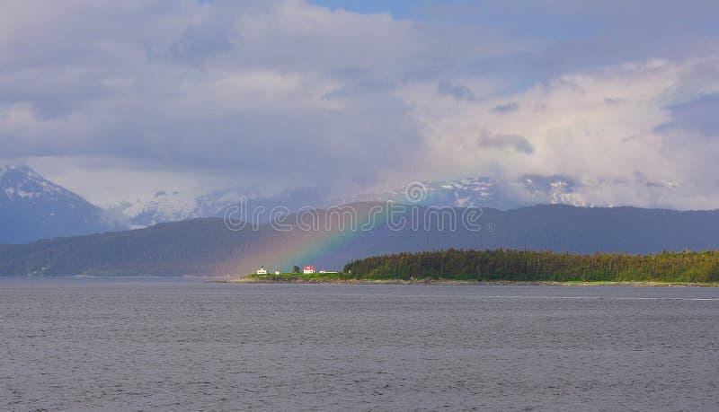 Arcobaleno sopra il faro della ritirata del punto immagine stock