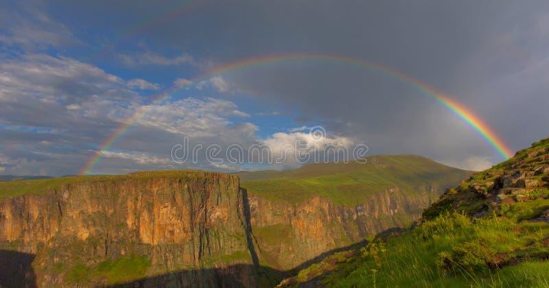 Arcobaleno sopra le montagne verdi fotografie stock