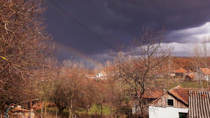Arcobaleno sul cielo soleggiato scuro fotografia stock libera da diritti