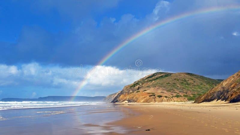 Arcobaleno sulla spiaggia di Vale Figueiras nel Portogallo immagine stock