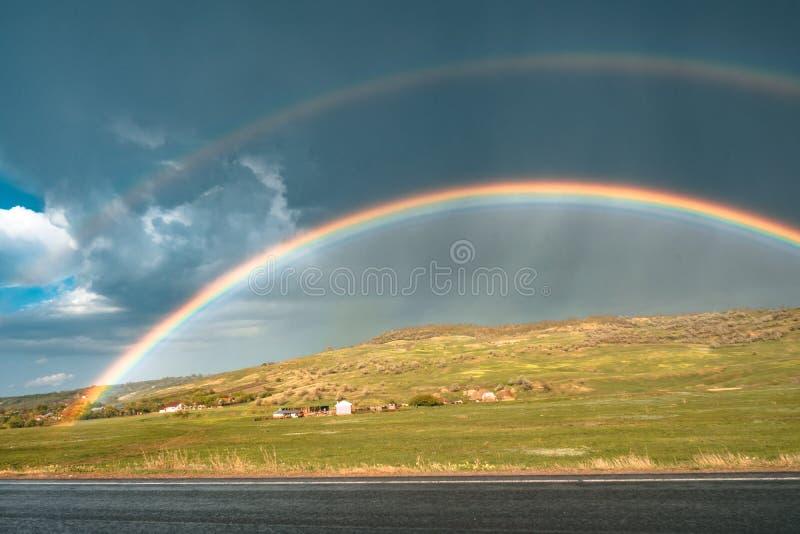 Arcobaleno sulla strada con le nuvole sul cielo fotografia stock