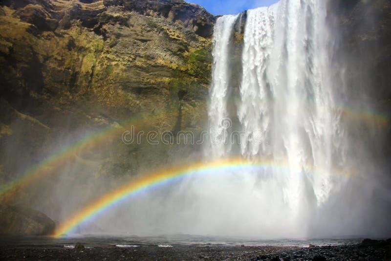 Arcos-íris dobro na cachoeira de Skogafoss em Islândia imagem de stock