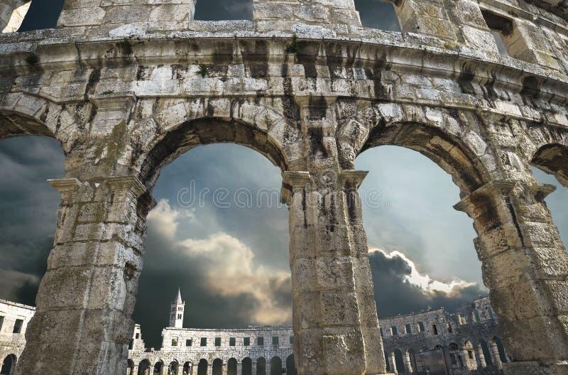 Arcos del amphitheatre de las pulas con el fondo del cielo del trueno imagenes de archivo