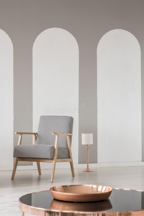 Arcs dans un intérieur moderne de salon avec un rétros fauteuil et plan rapproché d'un plat de cuivre sur une table Photo réelle images stock