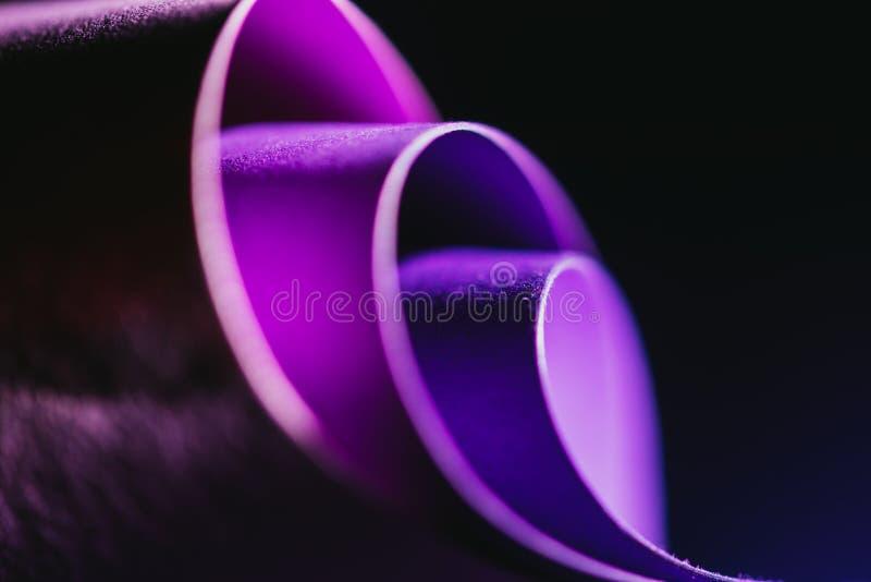 Arcs of purple paper on black stock image