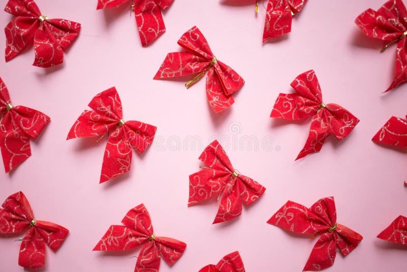 Arcs rouges modèle, ensemble de satin de Noël de rubans sur le fond rose photographie stock