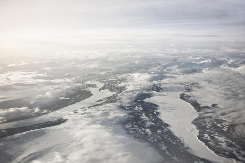Arctic Circle - Frozen Lands and Rivers. Majestic aerial view of frozen Northern Sweden. High mountain ranges and frozen rivers and lakes with low clouds royalty free stock image
