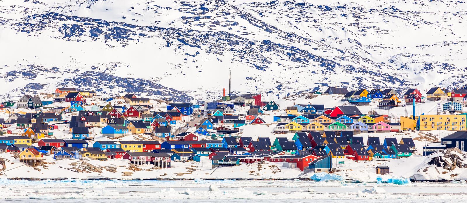 Arctic city center panorama with colorful Inuit houses on the rocky hills covered in snow with snow and mountain in the background. Ilulissat, Avannaata royalty free stock image