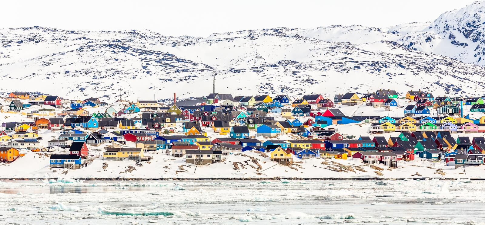 Arctic city center panorama with colorful Inuit houses on the rocky hills covered in snow with snow and mountain in the background. Ilulissat, Avannaata royalty free stock photos