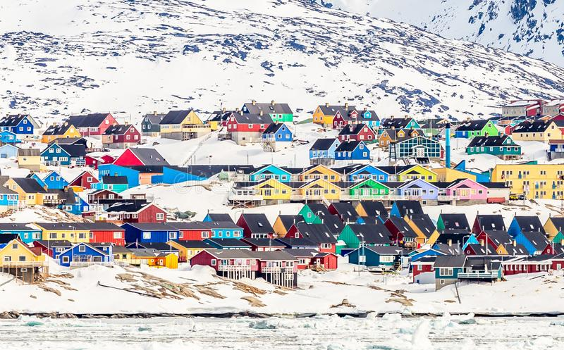 Arctic city center panorama with colorful Inuit houses on the rocky hills covered in snow with snow and mountain in the background. Ilulissat, Avannaata stock photos