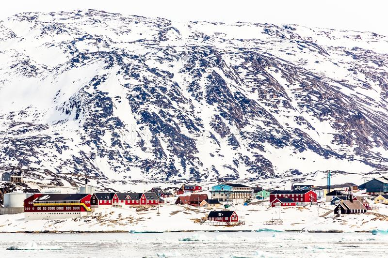 Arctic city panorama with colorful Inuit cottages and oil factory on the rocky hills covered in snow and mountain in the. Background, Ilulissat, Avannaata royalty free stock photo