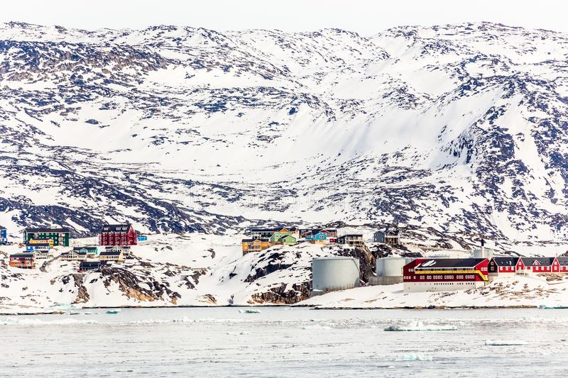 Arctic city panorama with colorful Inuit cottages and oil factory on the rocky hills covered in snow and mountain in the. Background, Ilulissat, Avannaata stock images
