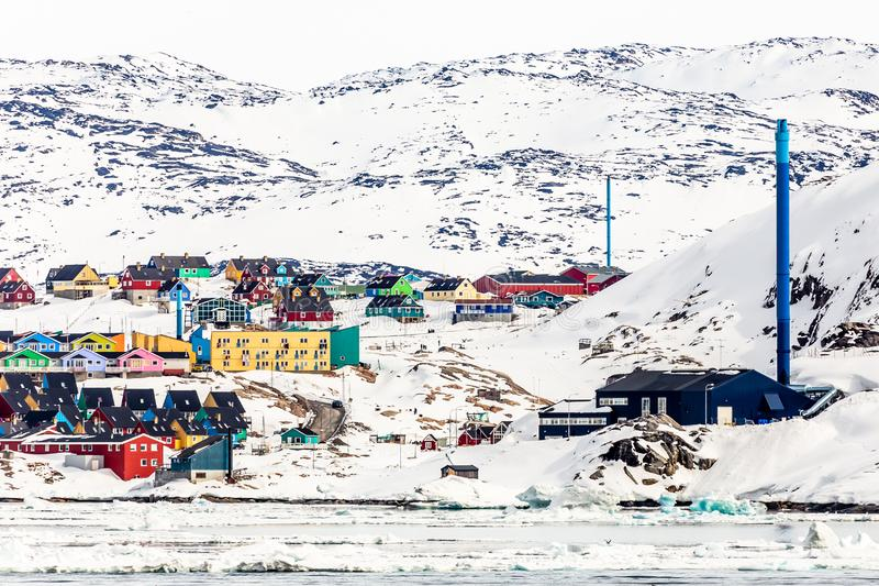 Arctic city panorama with colorful Inuit cottages and powerplant on the rocky hills covered in snow and mountain in the background. Ilulissat, Avannaata stock image