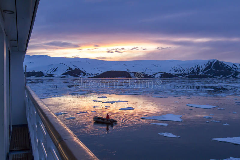Arctic Glow reflecting in Whalers Bay, Deception Island, Antarctica with Zodiac and ship deck stock image