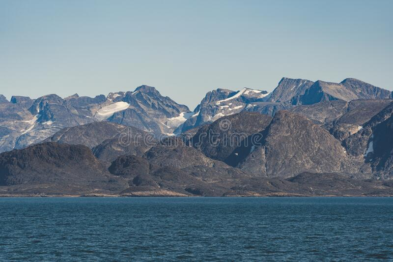 Arctic landscape of Greenland on a sunny day in Summer. Beautiful view of mountains with Snowy peaks and Glaciers along. The Atlantic Ocean. Photo taken in royalty free stock image