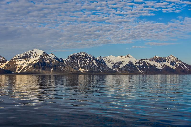Arctic landscape with mountains in Svalbard with reflection. Arctic landscape with glacier in Svalbard, Norway at summer time. With beautiful reflrction stock image
