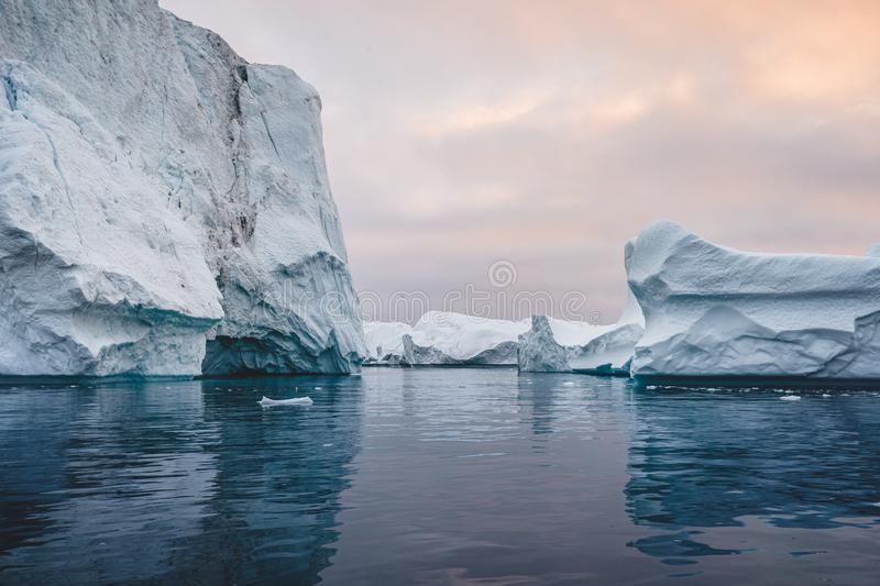 Arctic nature landscape with icebergs in Greenland icefjord with midnight sun sunset sunrise in the horizon. Early royalty free stock images