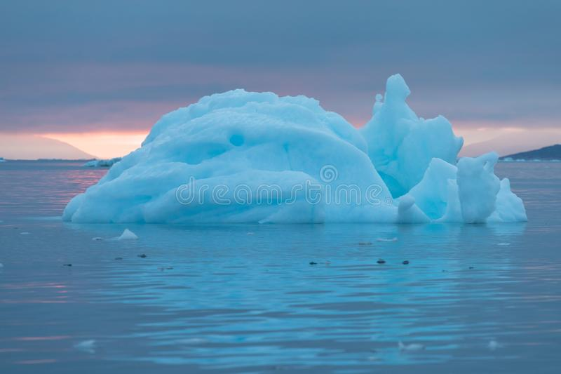 Arctic nature landscape with icebergs in Greenland icefjord with midnight sun sunset / sunrise in the horizon.  Early morning. Arctic nature landscape with royalty free stock photos