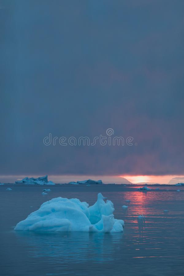 Arctic nature landscape with icebergs in Greenland icefjord with midnight sun sunset / sunrise in the horizon.  Early morning. Arctic nature landscape with royalty free stock photography