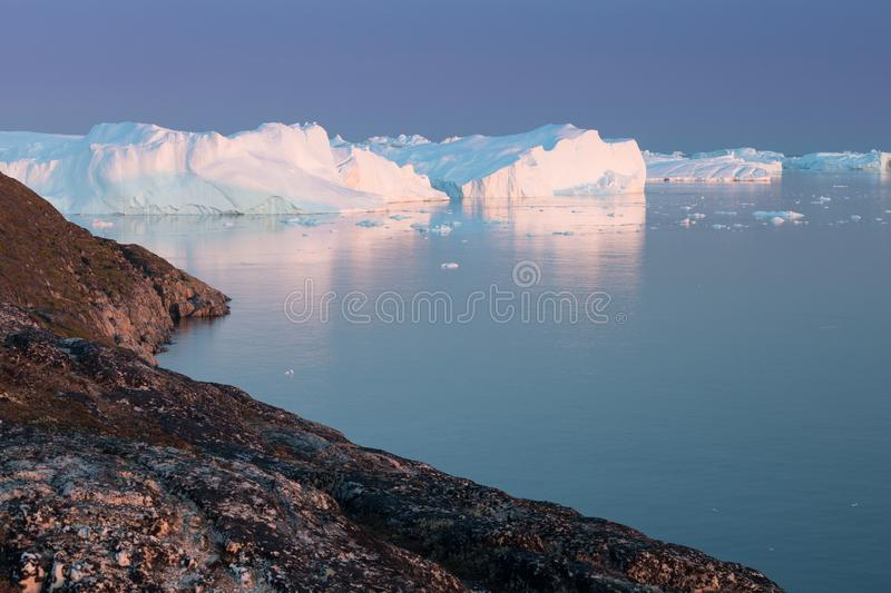 Arctic nature landscape with icebergs in Greenland icefjord with midnight sun sunset / sunrise in the horizon.  Early morning. Arctic nature landscape with royalty free stock image