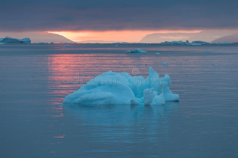 Arctic nature landscape with icebergs in Greenland icefjord with midnight sun sunset / sunrise in the horizon.  Early morning. Arctic nature landscape with stock photos