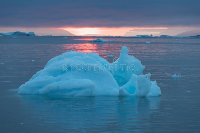 Arctic nature landscape with icebergs in Greenland icefjord with midnight sun sunset / sunrise in the horizon.  Early morning. Arctic nature landscape with stock photography